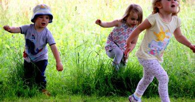 Children running through grasss in the Lustleigh Orchard
