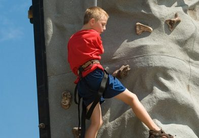 A boy climbs a mobile climbing wall