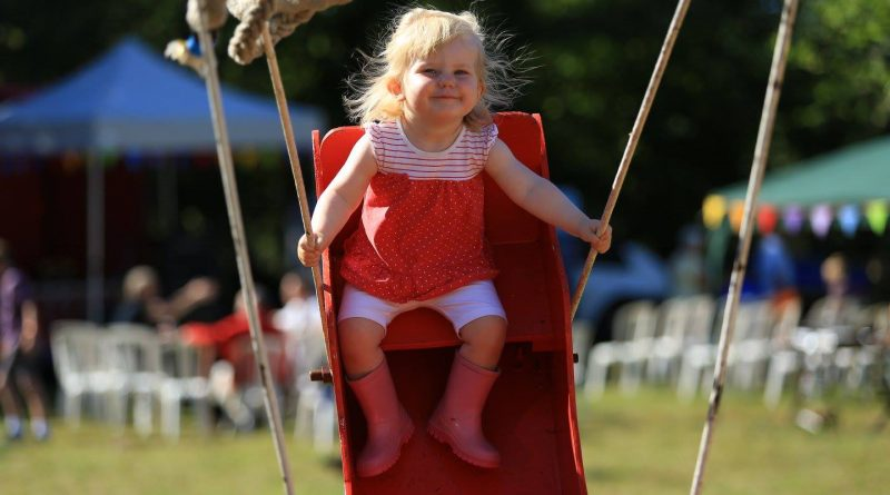 A young blonde girl rides on a swingboat at the Lustleigh Village Show