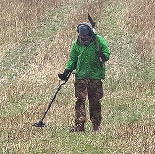 A man with a metal detector crosses a field in Devon