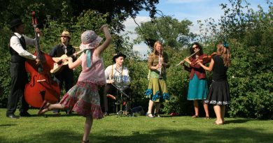 A young girl dances in a field as the band Hazaar! play